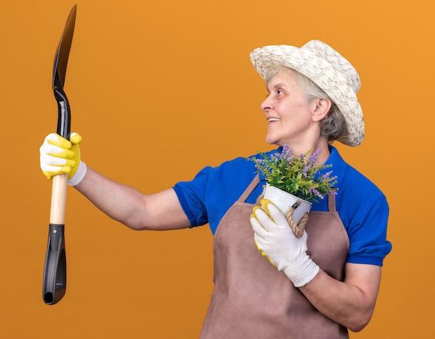 Jardineira idosa sorridente usando luvas e chapéu de jardinagem, segurando um vaso de flores e olhando para a pá