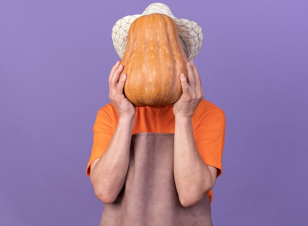 Jardineira idosa usando chapéu de jardinagem segurando uma abóbora na frente do rosto