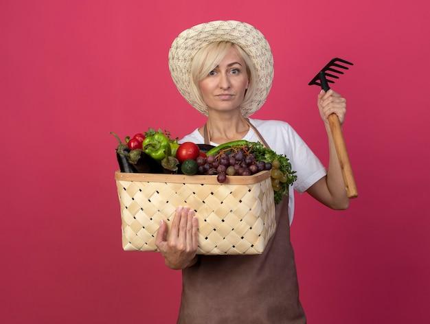 Jardineira loira de meia-idade confiante de uniforme, usando um chapéu segurando uma cesta de legumes e um ancinho olhando para a frente, isolada na parede carmesim com espaço de cópia