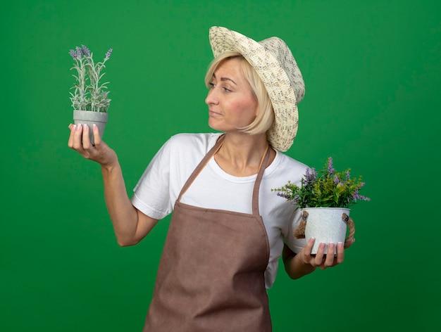 Jardineira loira de meia-idade confusa, de uniforme, usando um chapéu, segurando vasos de flores, olhando para uma delas isolada na parede verde