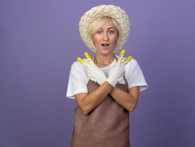 Jardineira loira de meia-idade impressionada de uniforme, usando chapéu e luvas de jardinagem, de mãos cruzadas, fazendo o sinal da paz isolado na parede roxa com espaço de cópia