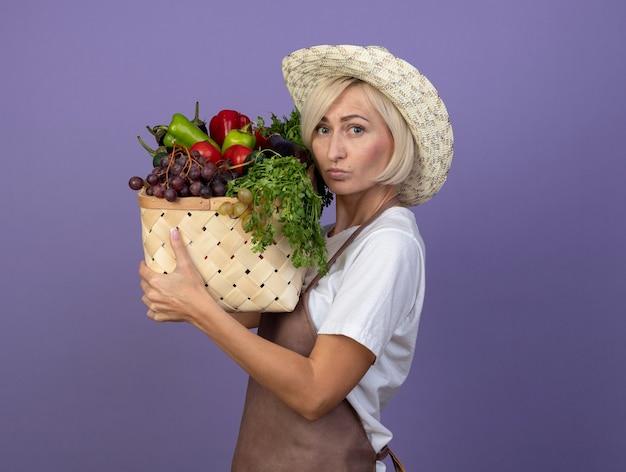 Jardineira loira de meia-idade pensativa de uniforme e chapéu