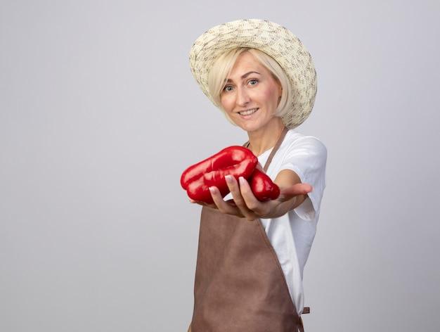 Jardineira loira de meia-idade sorridente, de uniforme, usando um chapéu em pé na vista de perfil, estendendo os pimentões em direção à câmera, isolada na parede branca com espaço de cópia