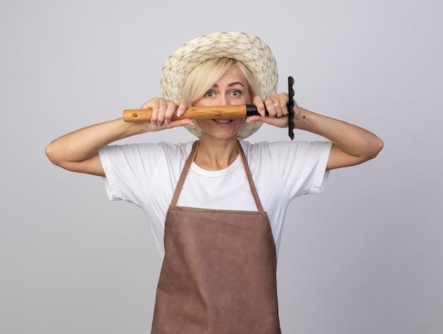 Jardineira loira de meia-idade sorridente, de uniforme, usando um chapéu, segurando o ancinho na frente do rosto, olhando para a frente, isolada na parede branca