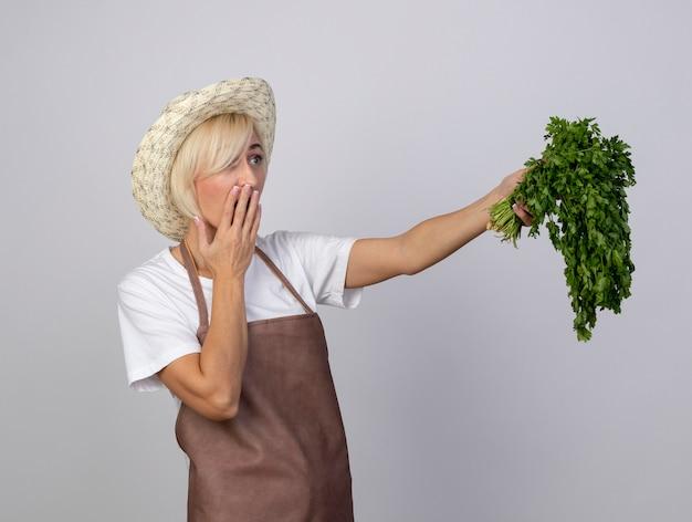 Jardineira loira de meia-idade, uniformizada, usando um chapéu em pé na vista de perfil, estendendo-se por um ramo de coentro, olhando em linha reta, mantendo a mão na boca