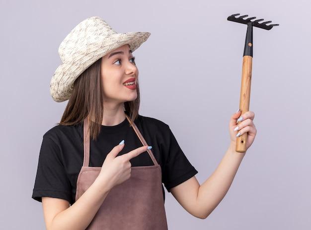 Jardineira muito caucasiana ansiosa com chapéu de jardinagem, segurando e apontando para o ancinho isolado na parede branca com espaço de cópia