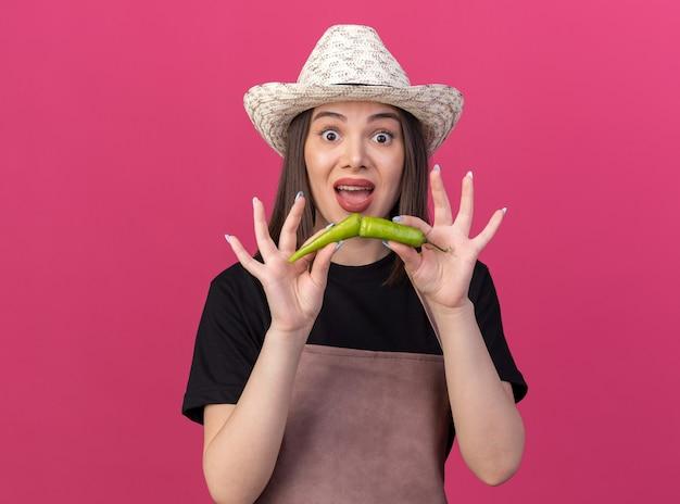 Jardineira muito caucasiana ansiosa com chapéu de jardinagem segurando pimenta quebrada isolada na parede rosa com espaço de cópia