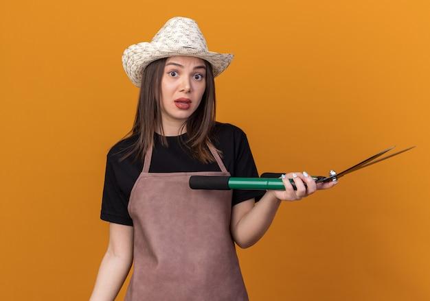 Jardineira muito caucasiana ansiosa com chapéu de jardinagem segurando uma tesoura de jardinagem isolada na parede laranja com espaço de cópia