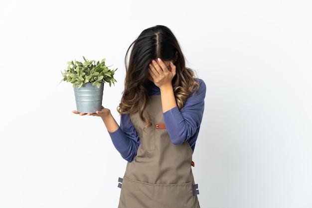 Jardineira segurando uma planta isolada com uma expressão cansada e doente