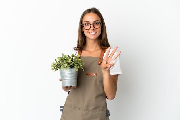 Jardineira segurando uma planta sobre um fundo branco isolado feliz e contando três com os dedos