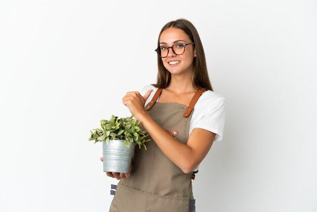 Jardineira segurando uma planta sobre um fundo branco isolado, orgulhosa e satisfeita