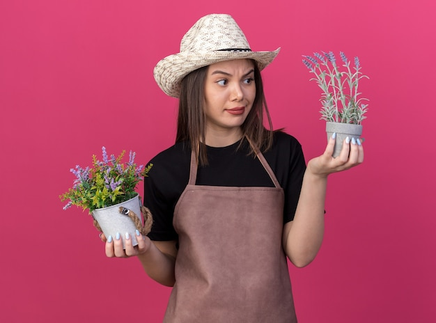 Jardineira sem noção, bonita e caucasiana, usando um chapéu de jardinagem, segurando e olhando vasos de flores
