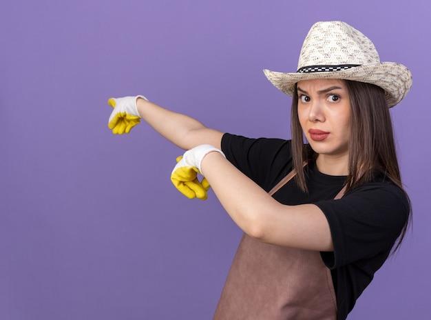 Jardineira séria, bonita, caucasiana, usando chapéu de jardinagem e luvas apontando para o lado