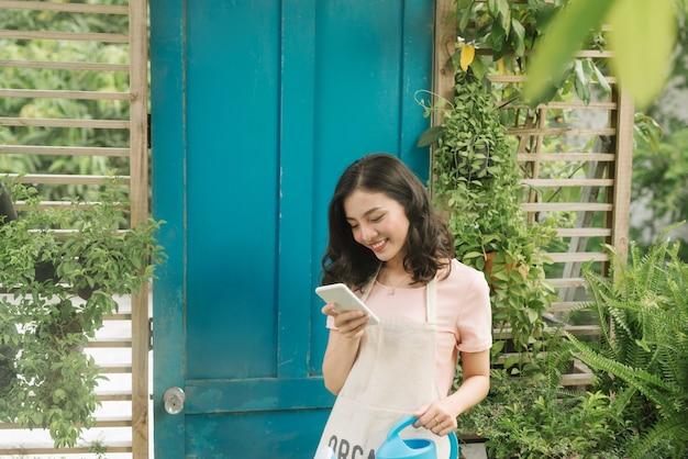 Jardineira usando celular enquanto rega no jardim