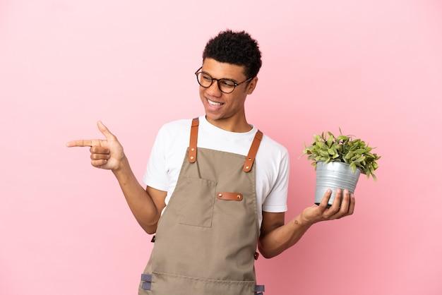 Jardineiro africano segurando uma planta isolada em um fundo rosa apontando o dedo para o lado e apresentando um produto
