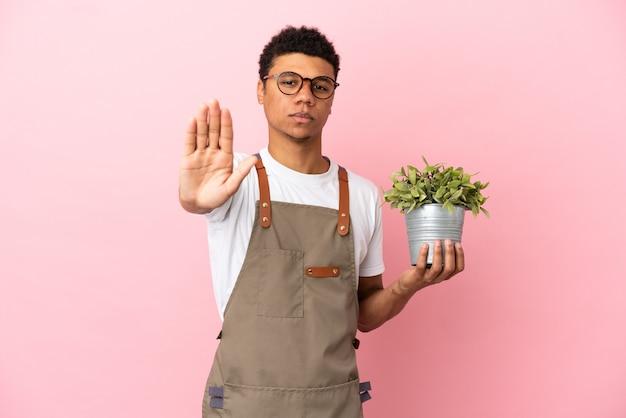Jardineiro africano segurando uma planta isolada em um fundo rosa, fazendo um gesto de pare