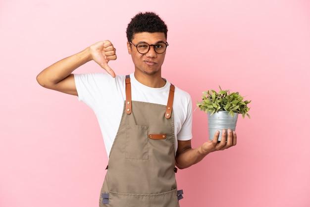 Jardineiro africano segurando uma planta isolada em um fundo rosa, mostrando o polegar para baixo com expressão negativa
