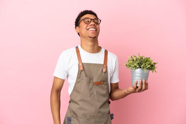 Jardineiro africano segurando uma planta isolada em um fundo rosa rindo
