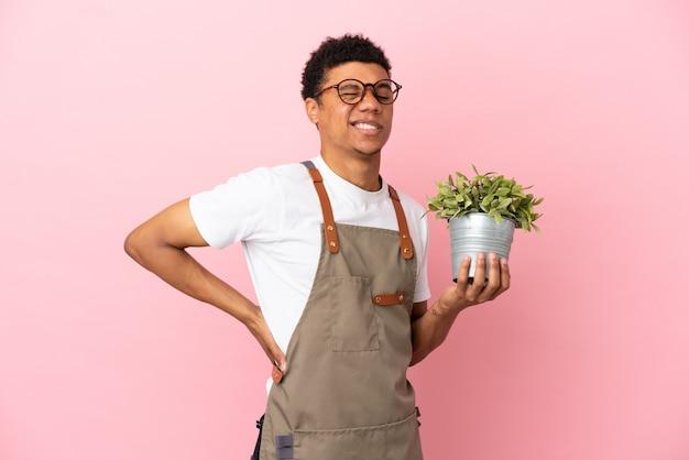 Jardineiro africano segurando uma planta isolada em um fundo rosa sofrendo de dor nas costas por ter feito um esforço