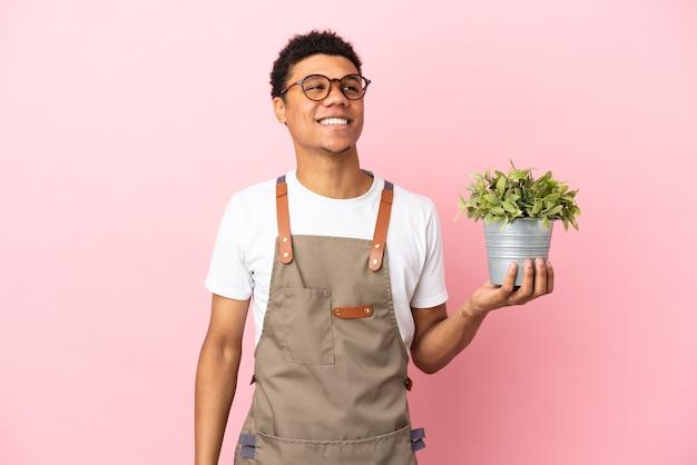Jardineiro africano segurando uma planta isolada em um fundo rosa tendo uma ideia enquanto olha para cima