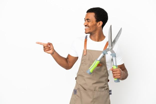 Jardineiro afro-americano segurando uma tesoura de poda sobre um fundo branco isolado, apontando o dedo para o lado e apresentando um produto