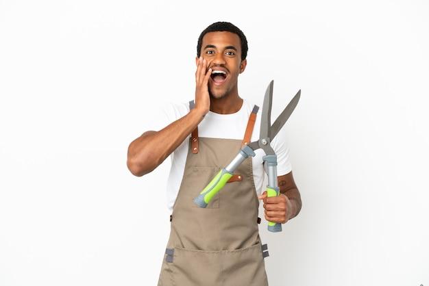 Jardineiro afro-americano segurando uma tesoura de poda sobre um fundo branco isolado com expressão facial de surpresa e choque