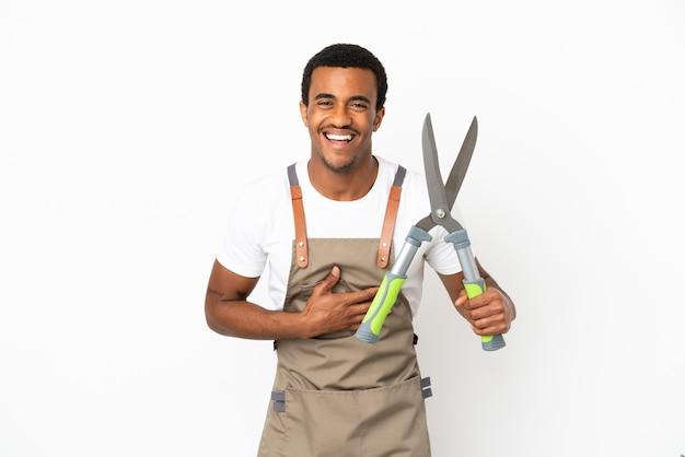 Jardineiro afro-americano segurando uma tesoura de poda sobre um fundo branco isolado e sorrindo muito