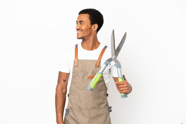 Jardineiro afro-americano segurando uma tesoura de poda sobre um fundo branco isolado, olhando para o lado