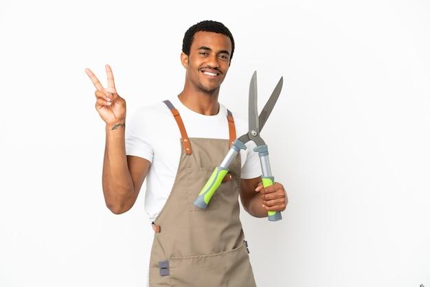 Jardineiro afro-americano segurando uma tesoura de poda sobre um fundo branco isolado, sorrindo e mostrando o sinal da vitória