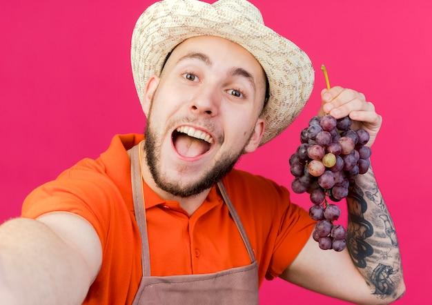 Jardineiro alegre usando chapéu de jardinagem segurando uvas e fingindo segurar a câmera