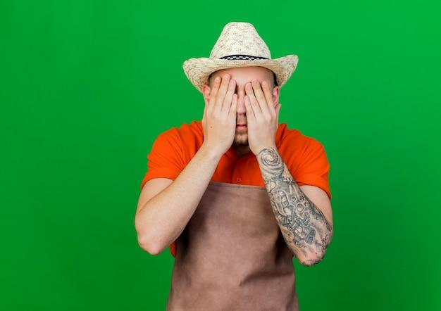 Jardineiro assustado usando chapéu de jardinagem fecha os olhos com as mãos