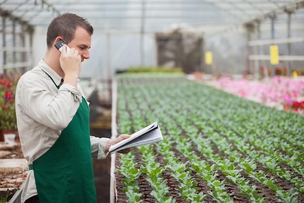 Jardineiro chamando e tomando notas em casa de vegetação