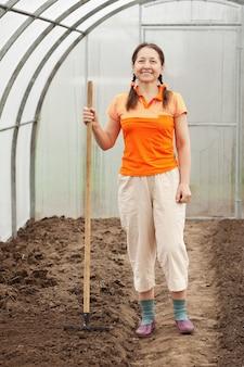 Jardineiro com ancinho em estufa