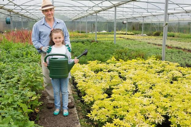 Jardineiro com neta segurando lata de rega