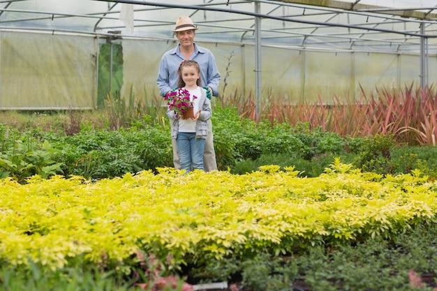 Jardineiro com neto segurando flor roxa