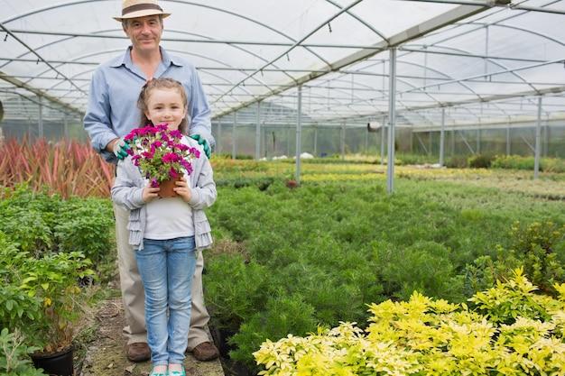 Jardineiro com uma neta segurando um vaso de flores