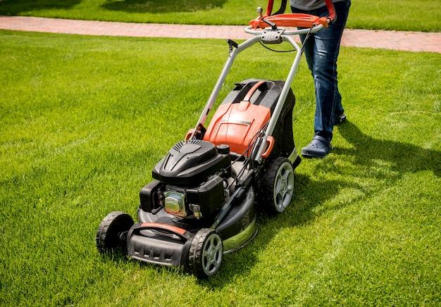 Jardineiro cortando a grama. projeto da paisagem. fundo verde Foto Premium