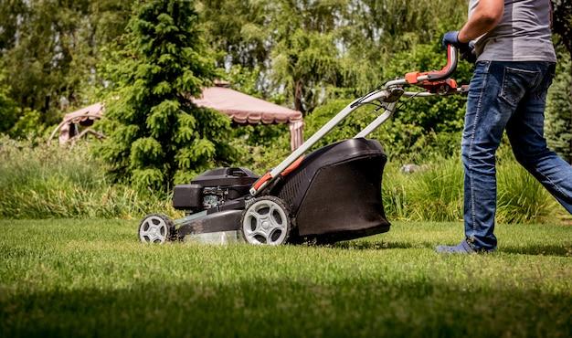 Jardineiro cortando a grama. projeto da paisagem.