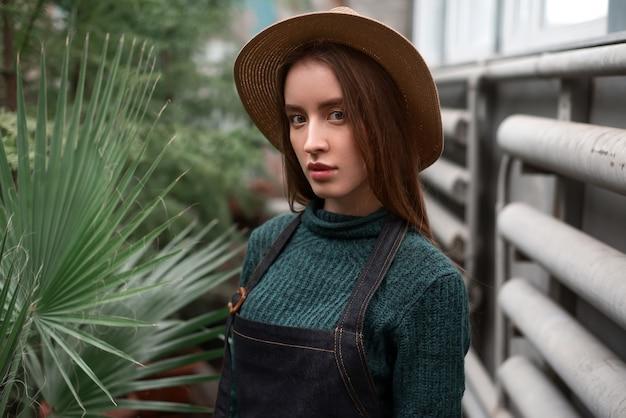 Jardineiro de chapéu e avental contra plantas verdes