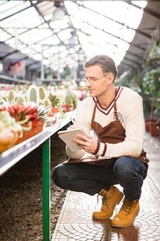 Jardineiro de homem bonito olhando cactos e fazendo anotações em caderno no laranjal