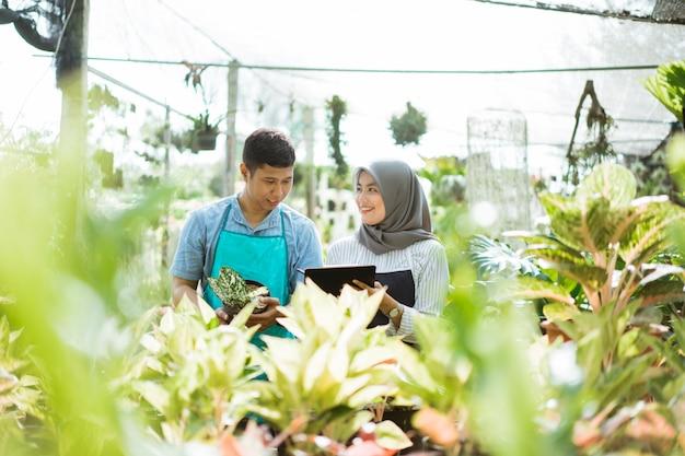 Jardineiro de homem e mulher verificar as plantas