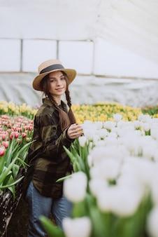 Jardineiro de jovem cuidando de flores de tulipas cultivadas em uma estufa.