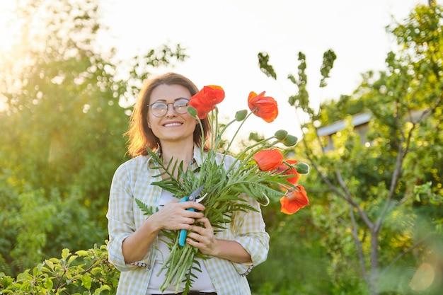 Jardineiro de mulher cortando papoulas de flores vermelhas com tesouras de jardim, dia ensolarado no jardim de primavera, feliz linda fêmea madura com buquê