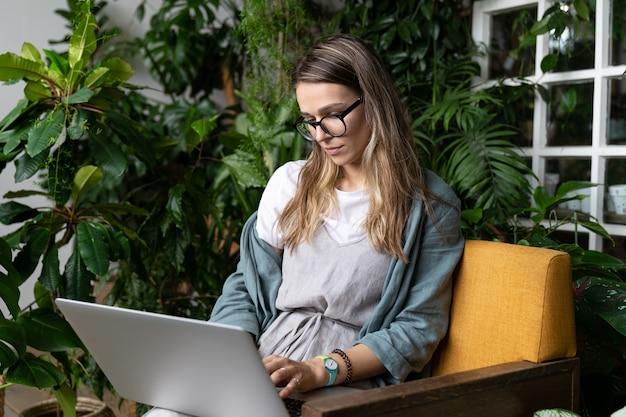 Jardineiro de mulher usa vestido de linho, sentado na cadeira em uma casa verde, trabalhando no laptop, rodeado por plantas. horta doméstica, trabalho remoto, trabalho à distância.