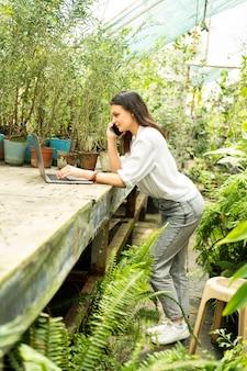 Jardineiro de mulheres de negócios atraente falando no telefone, usando o laptop em estufa.