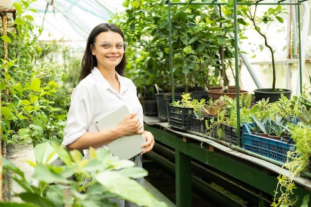 Jardineiro de mulheres de negócios atraente jovem em copos com tablet sorrindo em estufa.