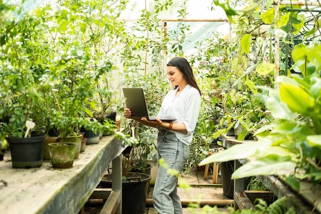 Jardineiro de mulheres de negócios atraente usando laptop. tecnologia moderna em jardinagem.