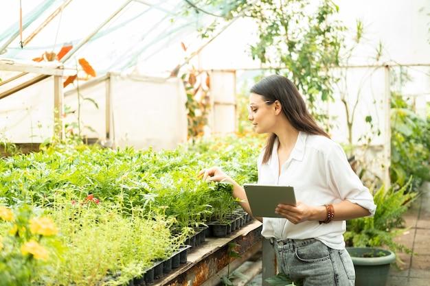 Jardineiro de mulheres de negócios atraentes de óculos usando tecnologia moderna de tablet em negócios de jardinagem