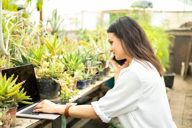Jardineiro de mulheres de negócios atraentes falando ao telefone usando um laptop em uma estufa