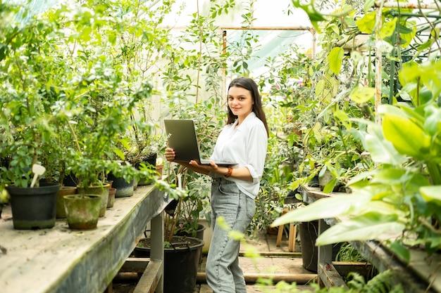 Jardineiro de mulheres de negócios atraentes usando tecnologia moderna de laptop em negócios de jardinagem